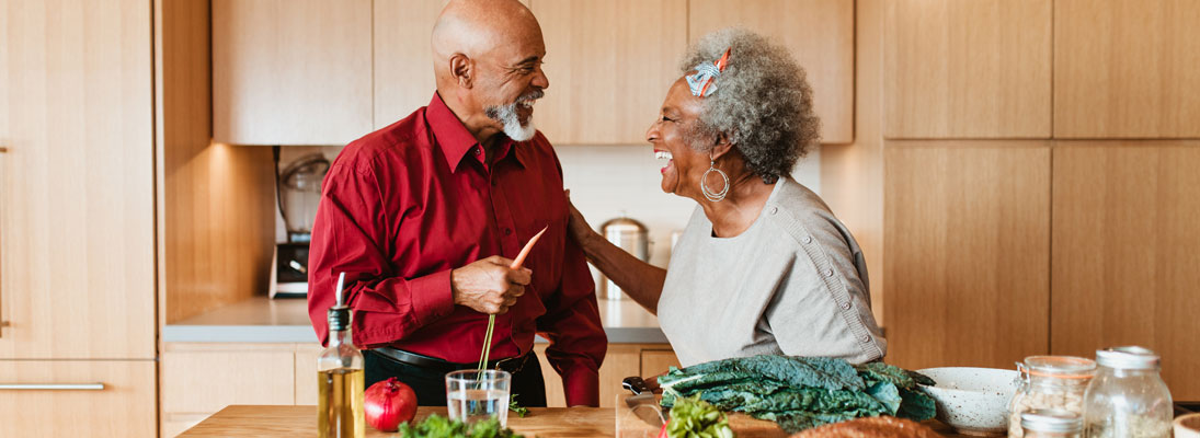man and woman preparing healthy food and laughing