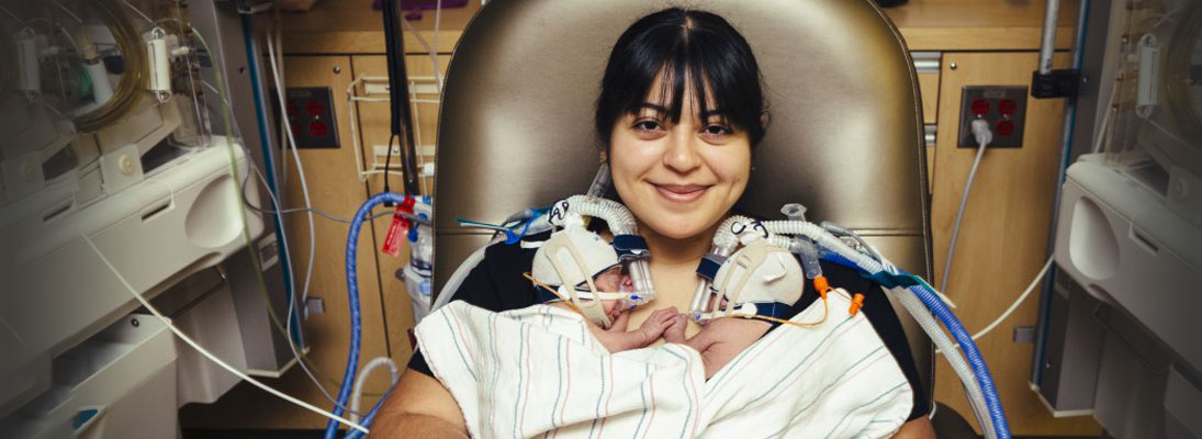 a mother holds her newborn twins to her chest