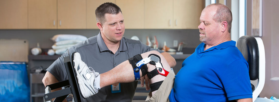 a male physical therapist assists a man with a brace on his leg