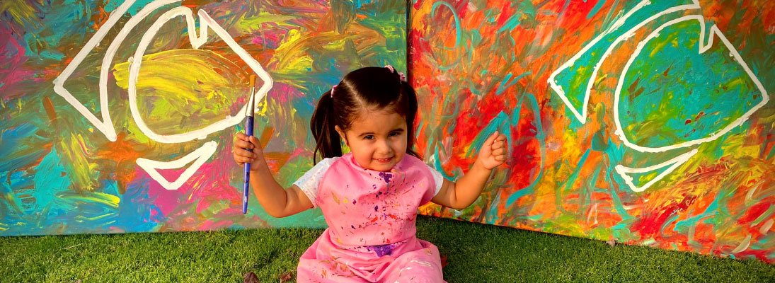 3-year-old Emmy Lovik sits in front of her artwork