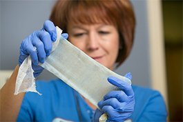 Sandra Yovino, RN, director of Community Regional's burn center, inspects a new kind of replacement skin graft .