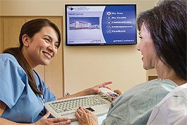 A nurse at Clovis Community Medical Center shows a new patient how to use the interactive GetWell Network to learn about her procedure, medications and hospital safety, and how to give staff feedback through her keyboard or TV remote control.