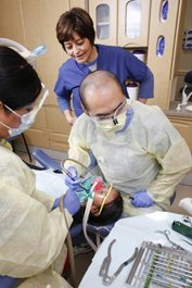 Rosaura Pacheco, DDS, FACD, a faculty member of the dental residency program, supervises dental resident Dr. Paul Hsiao as he performs a root canal on a 10-year-old girl.