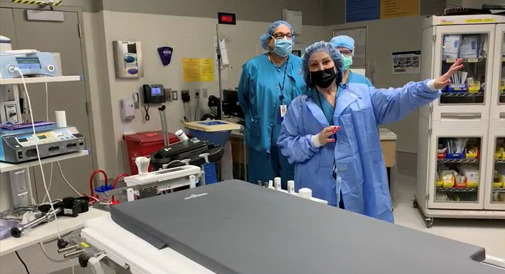 Masked doctor stands in operating room with her surgical team
