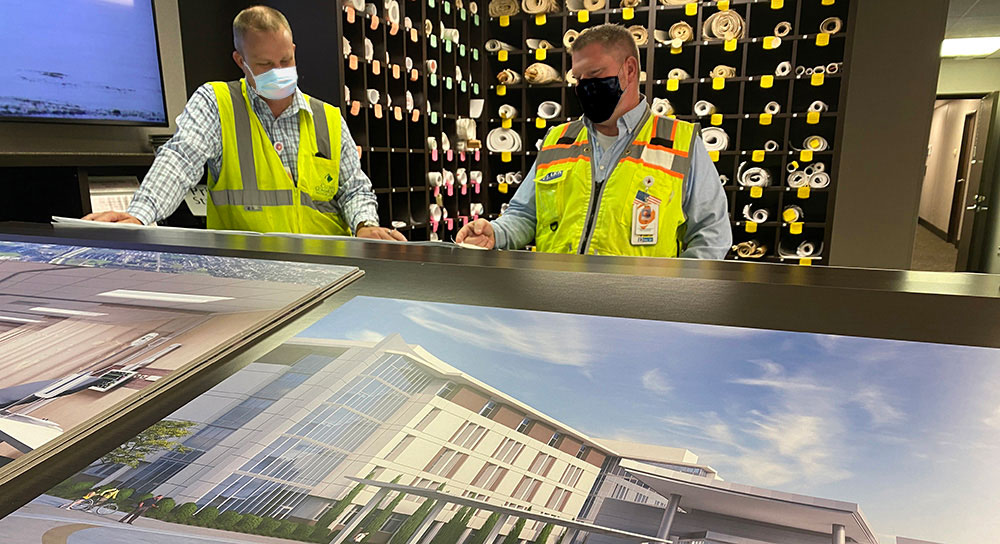 two men look over plans to add an oxygen tank to the hospital