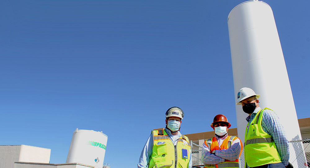Three men in masks and hard hats stand in front of oxygen tanks