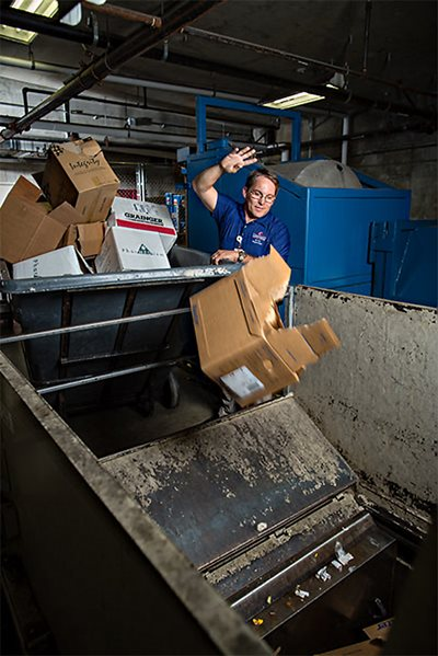 Environmental Services supervisor James Norton tosses boxes into a compactor