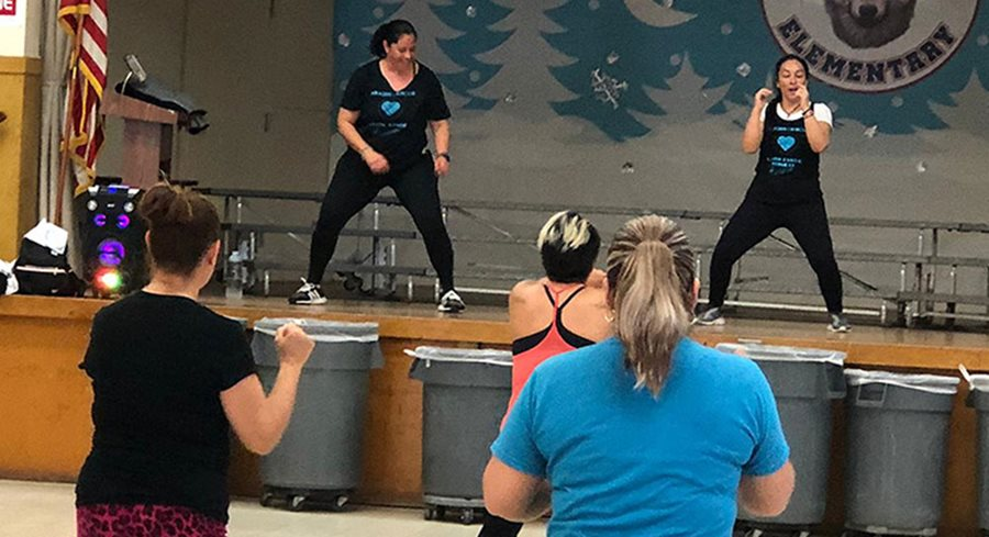 Two women on an elementary school stage lead a fitness class