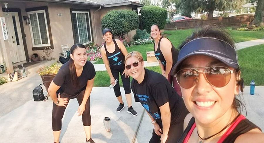 Five women in fitness gear strike a pose with their hands on their knees outside a house